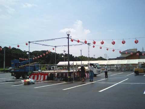雨上がり、係りの人達が盆踊り大会の会場を設営しています。