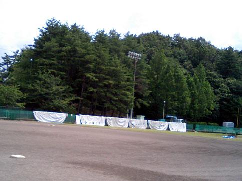 野球場内でテントを解体し、乾いていないテントをフェンスに掛けて乾かしています。